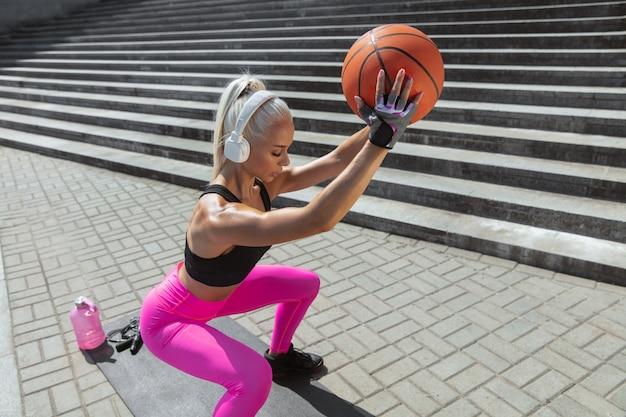 Una giovane donna atletica in camicia e cuffie bianche che risolvono ascoltando la musica all'aperto della via. fare squat con la palla. concetto di stile di vita sano, sport, attività, perdita di peso. Foto Gratuite