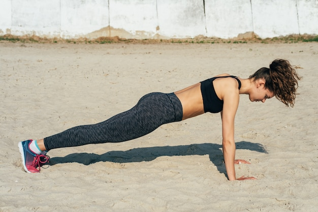 Young athletic woman in sportswear doing push-ups on the sand on a sunny morning Premium Photo