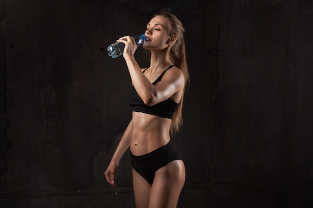 Young athletic woman in sportswear drinking water Premium Photo