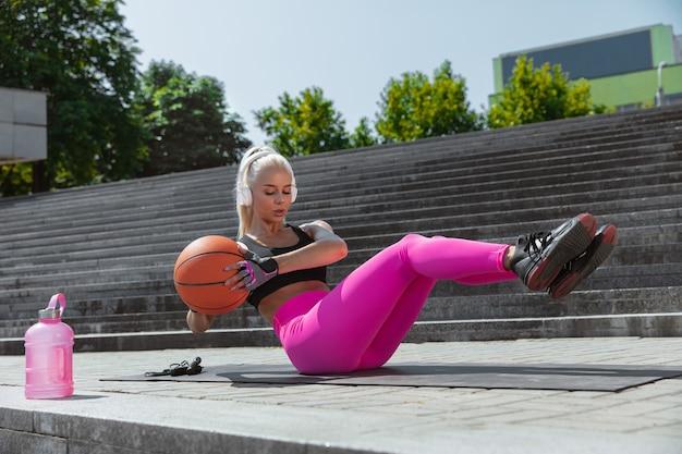 Una giovane donna atletica in formazione cuffie bianche Foto Gratuite