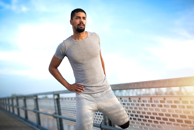 Giovane sportivo afroamericano attraente che riscalda le gambe prima di eseguire l'allenamento fitness e stile di vita attivo. Foto Gratuite