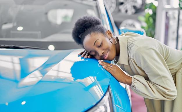 若い魅力的なアフロ女性は、新しい自動車の所有者であることを楽しんでいます Premium写真