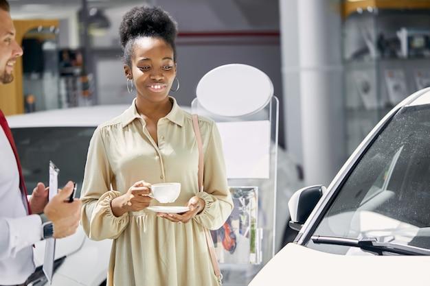 젊은 매력적인 아프리카 여자 새로운 자동차의 소유자가 되 고 즐길 프리미엄 사진