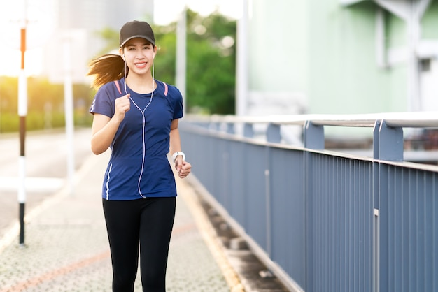 Young attractive asian runner woman running in city street Premium Photo