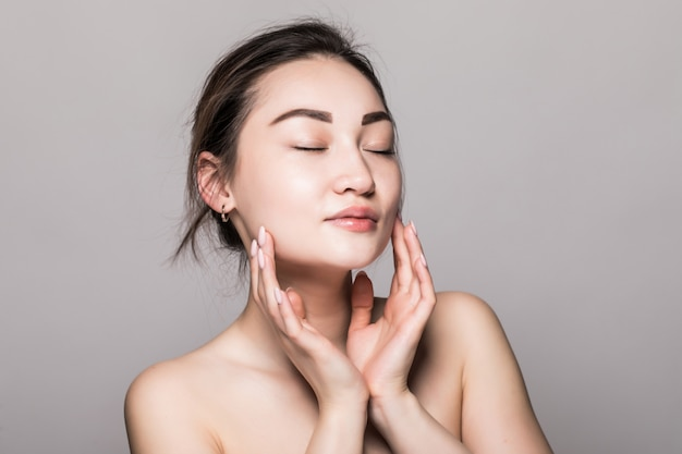 Young attractive asian woman skin care on gray wall Free Photo