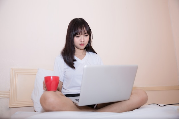Young attractive asian woman using laptop computer while lying on bed in casual clothes Free Photo