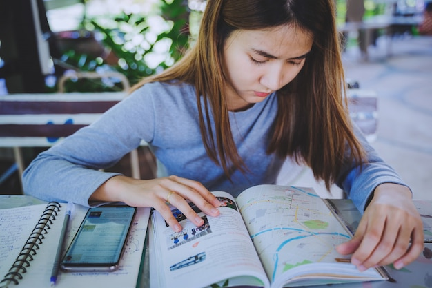 Young attractive asian women is using smartphone and travel book to planning about holiday Premium Photo