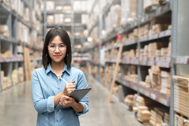 Young attractive asian worker, owner, entrepreneur woman holding smart tablet looking at camera. Premium Photo