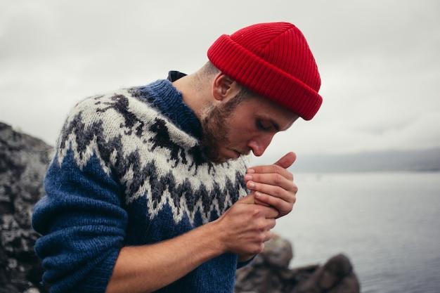 赤い漁師または船乗りのビーニー帽子と伝統的なアイスランドの装飾品の青いセーターの若い魅力的なひげを生やしたミレニアル世代の男 無料写真