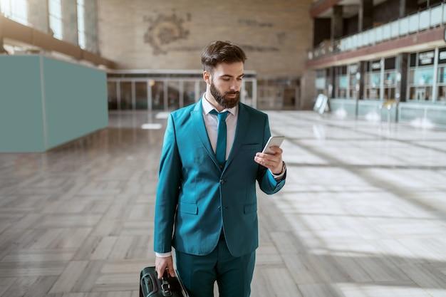 若い魅力的なひげを生やした青いスーツの荷物を運ぶと駅に立っている間スマートフォンを使用して真面目な実業家。出張のコンセプトです。 Premium写真