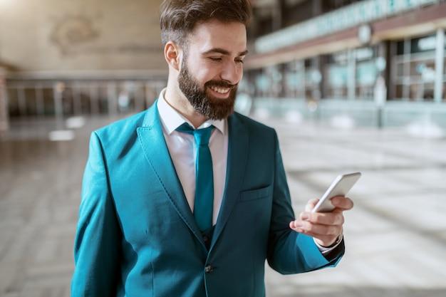 若い魅力的なひげを生やした笑みを浮かべてスーツを着て荷物を運ぶと駅に立っている間スマートフォンを使用しています。出張のコンセプトです。 Premium写真