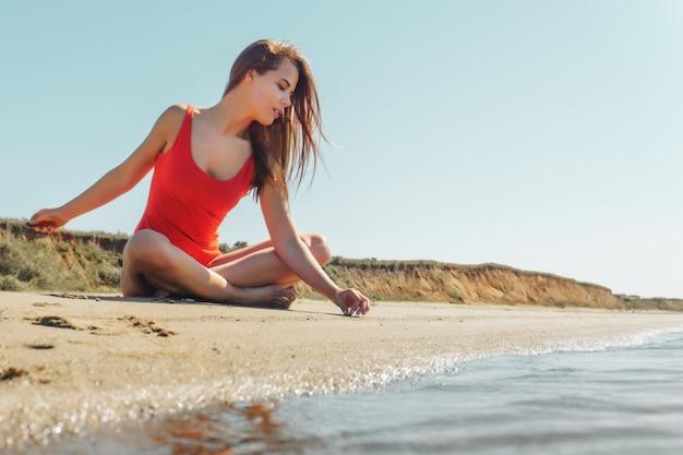 青い空と砂の上を書く赤いボディの若い魅力的なブルネットの女性 Premium写真