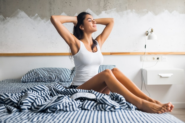 Young attractive brunette woman sitting on bed in pajamas and sleeping mask, smiling in bedroom, happy emotion, lazy in morning, waking up, sleepy, sexy, skinny legs Free Photo