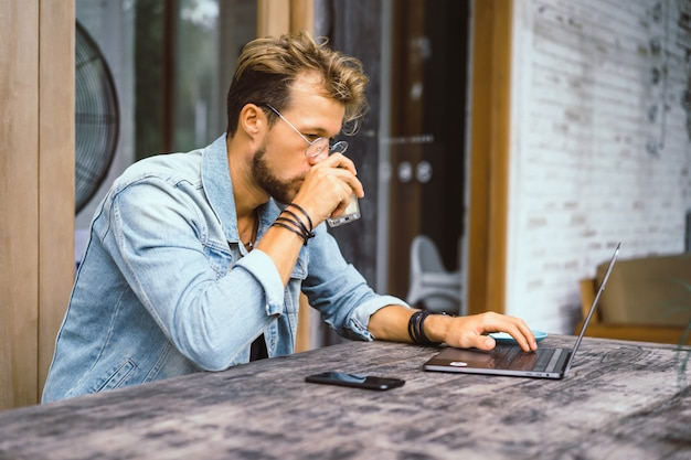 Young attractive business man in a cafe works for a laptop, drinks coffee. Free Photo