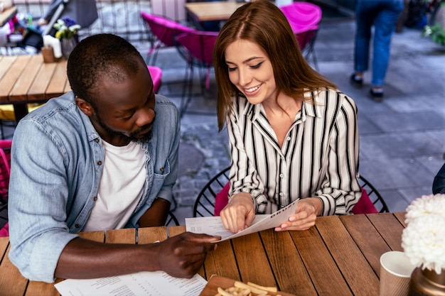 Young attractive caucasian girl and african boy are learning menu before ordering food Free Photo