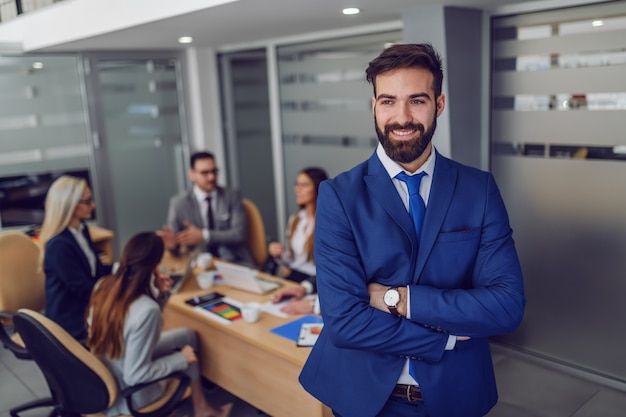 Young attractive caucasian smiling satisfied businessman in suit standing in boardroom with arms crossed Premium Photo
