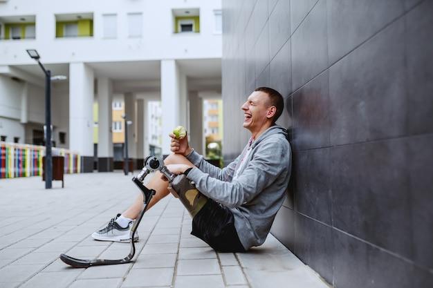 地面に座って、壁にもたれて、新鮮なリンゴを食べる義足の若い魅力的な白人スポーツマン。 Premium写真