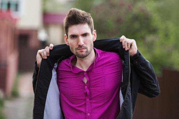 거리에 셔츠와 검은 자 켓을 입고 수염을 가진 검은 머리와 젊은 매력적인 쾌활 한 남자. 남성 스트리트 스타일. 봄의 자연. 도시를 산책 프리미엄 사진
