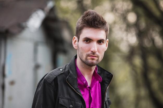 通りでシャツと黒いジャケットを身に着けているひげと黒髪の魅力的な陽気な若者。男性のストリートスタイル。春の自然。街歩き。 Premium写真