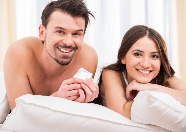 Young attractive couple in bed with a condom. Premium Photo