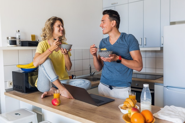 Giovani coppie attraenti dell'uomo e della donna che mangiano colazione insieme mattina alla cucina Foto Gratuite