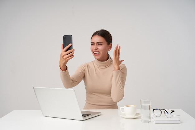 現代のラップトップでオフィスで働いて、エキサイティングな電話の会話をしながらスマートフォンで手を上げる若い魅力的な黒髪の女性 無料写真