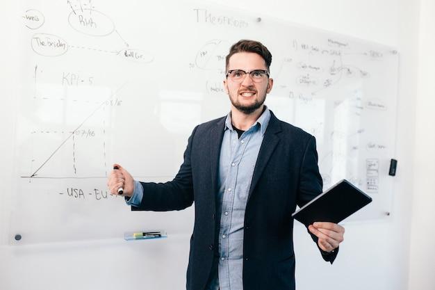 Молодой привлекательный темноволосый мужчина в очках стоит возле доски. он носит синюю рубашку и темную куртку. ему повезло с работой. Бесплатные Фотографии