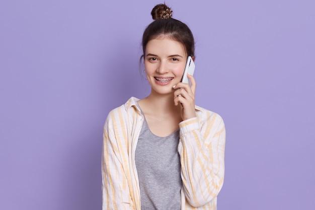 友人との会話を持つ携帯電話を持つ若い魅力的な暗い髪の若い女性 無料写真