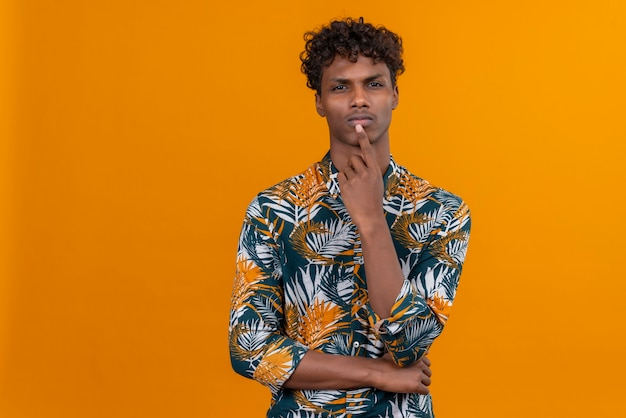 A young attractive dark-skinned man with curly hair in leaves printed shirt thinking while keeping hand on chin Free Photo
