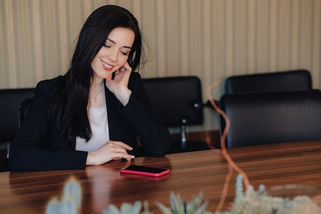 Young attractive emotional girl in business style clothes sitting at desk with phone in office or audience Premium Photo