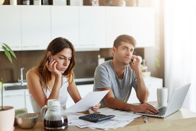 Young attractive european woman sitting at kitchen table next to her husband, reading attentively contract, calculating figures with calculator. handsome male making business call over cell phone Free Photo