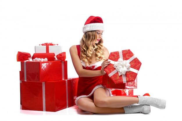 Молодая привлекательная женщина открывает рождественские подарки Бесплатные Фотографии