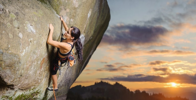 Young attractive female rock climber climbing challenging route on steep rock wall Premium Photo