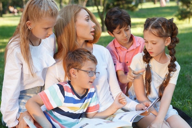 Young attractive female teacher reading a book to her little students Premium Photo