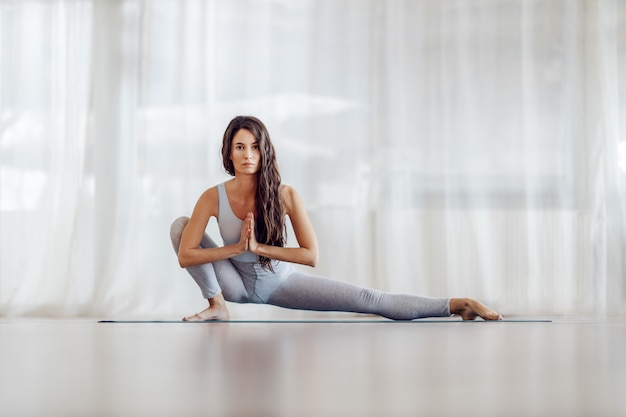 Young attractive fit slim girl with long hair in side lunge position. yoga studio interior. Premium Photo