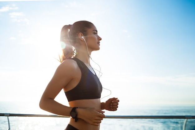 Young attractive fitness girl jogging with sea Free Photo