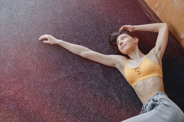 Young attractive fitness girl lying on the floor near the window on the background of a wooden wall Premium Photo