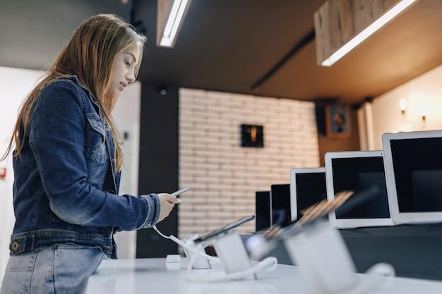 Giovane ragazza attraente nel negozio di elettronica sta alla scrivania e prova il telefono Foto Gratuite