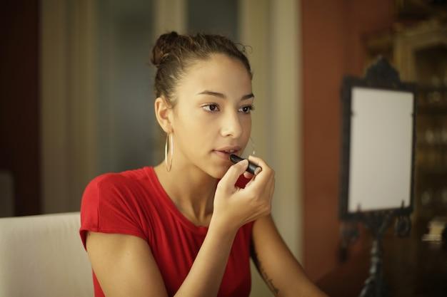 部屋の鏡の前で彼女の化粧を修正する魅力的な少女 無料写真