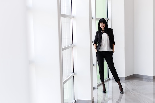 Young attractive happy brunette woman dressed in a black business suit Premium Photo