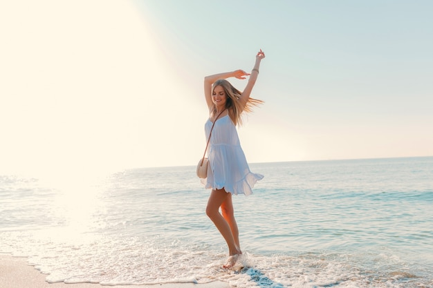 Young attractive happy woman dancing turning around by sea beach sunny summer fashion style in white dress vacation Free Photo