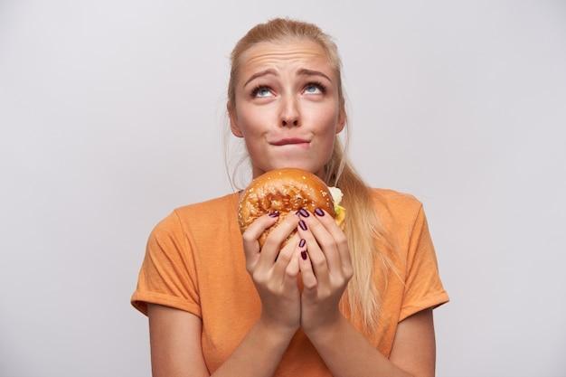 Молодая привлекательная длинноволосая блондинка с прической, сморщивающей лоб и кусающей нижнюю губу, при этом изящно глядя вверх с нездоровой пищей в руках, изолированные на белом фоне Бесплатные Фотографии