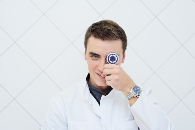 Young attractive male doctor dermatologist with dermatoscope in hand Premium Photo