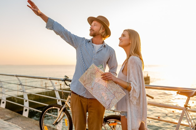 Молодой привлекательный мужчина и женщина, путешествующие на велосипедах, держа карту и осмотр достопримечательностей, романтическая пара на летних каникулах у моря на закате, друзья веселятся вместе Бесплатные Фотографии