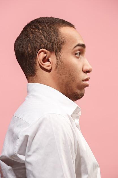 ピンクに分離されて驚いて探している若い魅力的な男 無料写真