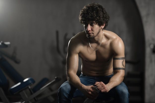Young attractive man resting in gym after exercising, male posing Premium Photo