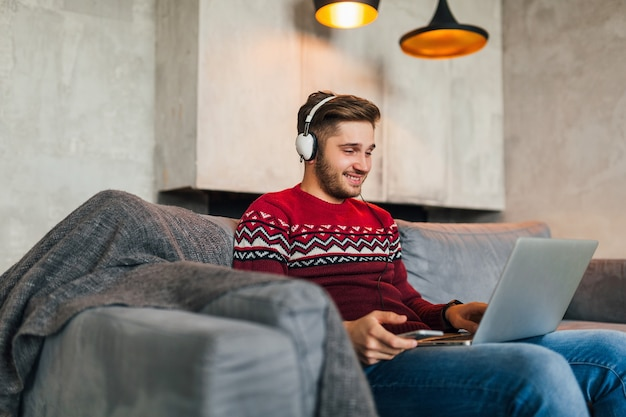 Young attractive man on sofa at home in winter with smartphone in headphones, listening to music, wearing red knitted sweater, working on laptop, freelancer, smiling, happy, positive, typing Free Photo
