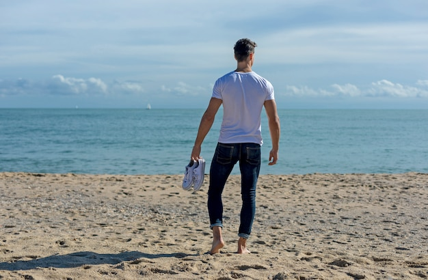 Young attractive man walking on seashore holding a pair of sneakers in a sunny day Premium Photo