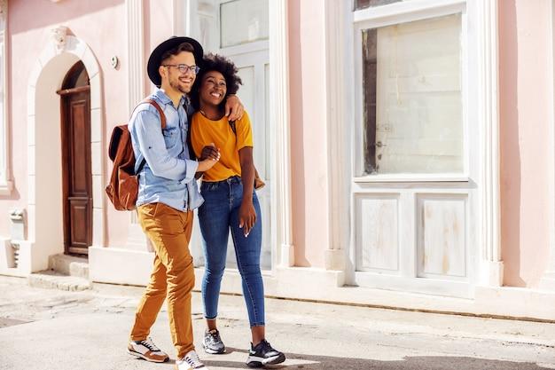 Молодая привлекательная многорасовая влюбленная пара гуляет на открытом воздухе и наслаждается прекрасным солнечным днем. Premium Фотографии