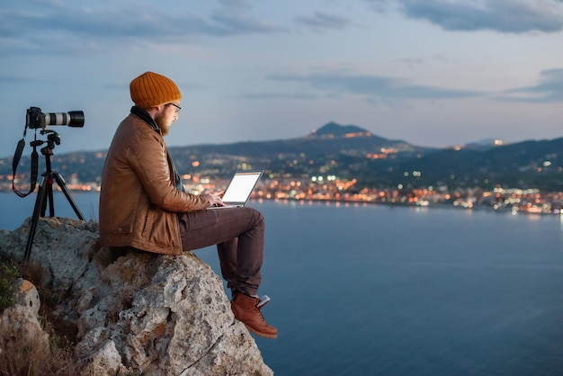Young attractive photographer sitting on rock and working on laptop with view of sea and mountains Premium Photo